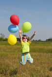 Happy little girl jumping with balloons. On meadow Royalty Free Stock Photography