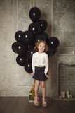 Happy little girl jumping with black balloons. Stock photo. Royalty Free Stock Image