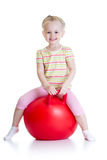 Happy little girl jumping on bouncing ball Stock Images