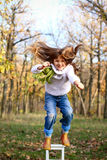 Happy little girl jumping from chair outdoors Royalty Free Stock Photo