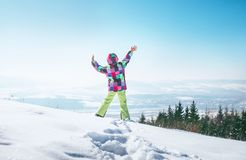 Happy little girl jumping on the deep snow hill with a great over city view stock images