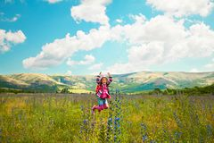 Happy little girl jumping on the field royalty free stock photos