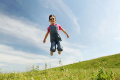 Happy little girl jumping high outdoors Royalty Free Stock Photo