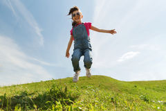 Happy little girl jumping high outdoors Stock Image