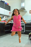 Happy girl. Is jumping in the kitchen Royalty Free Stock Image