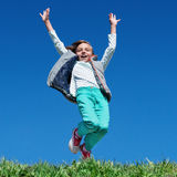 Happy little girl jumping on meadow Royalty Free Stock Photos
