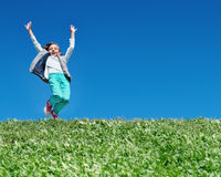 Happy little girl jumping on meadow Stock Photography