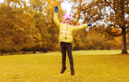 Happy little girl jumping outdoors. Autumn, childhood, happiness and people concept - happy little girl with raised hands jumping and having fun outdoors Stock Photos