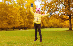 Happy little girl jumping outdoors. Autumn, childhood, happiness and people concept - happy little girl with raised hands jumping and having fun outdoors Stock Photography