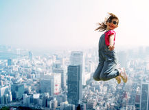 Happy little girl jumping over city background Stock Photography