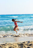 Happy Little Girl Jumping In Sea Waves. Jump Accompanied By Wate. R Splashes. Summer  Day, Ocean Coast Royalty Free Stock Images