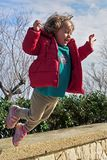 Happy Little Girl jumping and Smiling stock photo