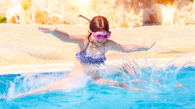 Happy little girl jumping to the pool Royalty Free Stock Photo