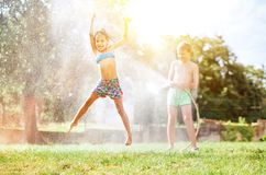 Happy little girl jumps under water, when brother pours her from garden hose. Hot summer days activity royalty free stock photos