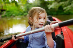 Happy little girl on a kayak on a river Royalty Free Stock Photos