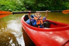 Happy little girl on a kayak on a river Stock Image