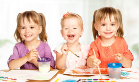 Happy little girl in kindergarten draw paints Royalty Free Stock Image