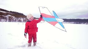 Happy little girl with a kite. Winter landscape