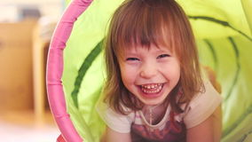 Happy little girl laughing in a children's toy tunnel