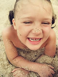 Happy little girl is laughing in summer. Happy little girl is laying on sand and laughing on the beach Stock Images