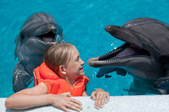 Happy Little Girl Laughing with two Dolphins in Swimming Pool Stock Image