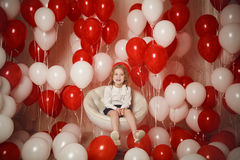 Happy little girl laughting with red and white balloons Royalty Free Stock Image