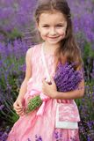 Happy little girl in lavender field with bouquet Royalty Free Stock Photography