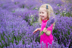 Happy little girl is in a lavender field Stock Photo