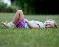 Happy Little Girl Laying in Grass Stock Image