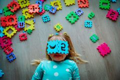 Happy little girl learn numbers and shapes, play with puzzle. Education concept royalty free stock photos
