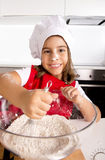 Happy little girl learning baking mixing flour in bowl wearing red apron and cook hat smiling satisfied Royalty Free Stock Photo