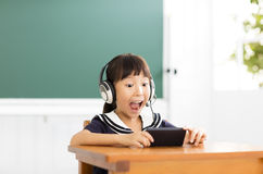 Happy little girl learning with smart phone in classroom Royalty Free Stock Photography