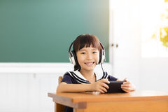 Happy little girl learning with smart phone in classroom Royalty Free Stock Photos