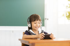 Happy little girl learning with smart phone in classroom Stock Images