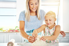 Happy little girl learning to make dough Stock Photography