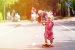 Happy little girl learning to ride scooter in the Royalty Free Stock Photos
