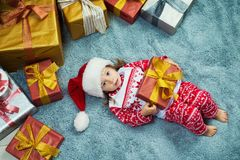 Happy little girl lies with a gift in her hands, top view, Christmas. Stock Image