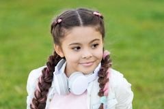 Happy little girl. little girl listen music. Kid in headset. Stylish child relax on green grass. Spring mood. Mp3 player royalty free stock images