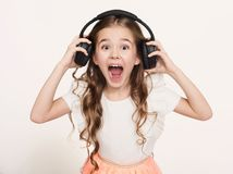 Happy little girl listen to music in headphones, white background. Happy little girl in headphones at white studio background. Portrait of child listening to royalty free stock images