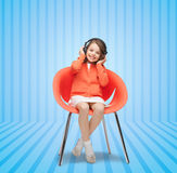 Happy little girl listening to music in headphones. People, leisure, hobby and entertainment concept - happy little girl listening to music in headphones over Royalty Free Stock Image