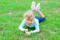Happy little girl with a lollipop lies on a green glade, free sp Stock Image