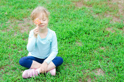 Happy little girl with a lollipop sitting on a green glade, free Stock Images