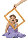 Happy little girl looking through the frame Stock Images
