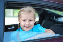 Happy little girl looking out of a car window Royalty Free Stock Image
