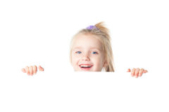 Happy little girl looking over empty board Royalty Free Stock Images