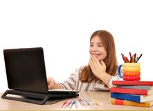 Little girl looks at something fun on the laptop Royalty Free Stock Photo