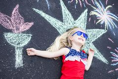 Happy little girl lying on asphalt with painted torch royalty free stock images