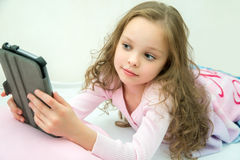 Happy little girl lying on bed with tablet computer Stock Image