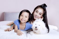 Little girl with mother and Maltese puppy. Happy little girl lying on the bedroom with her mother and Maltese puppy at home Stock Photography