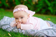 Happy little girl lying on a blanket in the park Stock Images